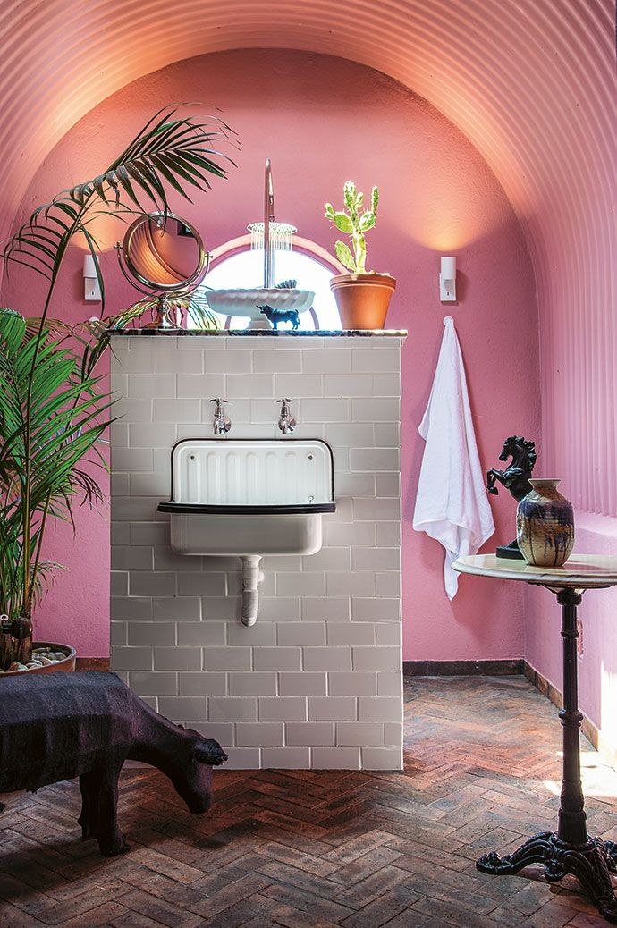 bathroom, grey herringbone floor tiles, pink wall, pink arch ceiling, white brick partition