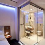 Bathroom, White Floor, White Wall, Glass Wall, White Toilet, White Sink, Wooden Floating Shelves