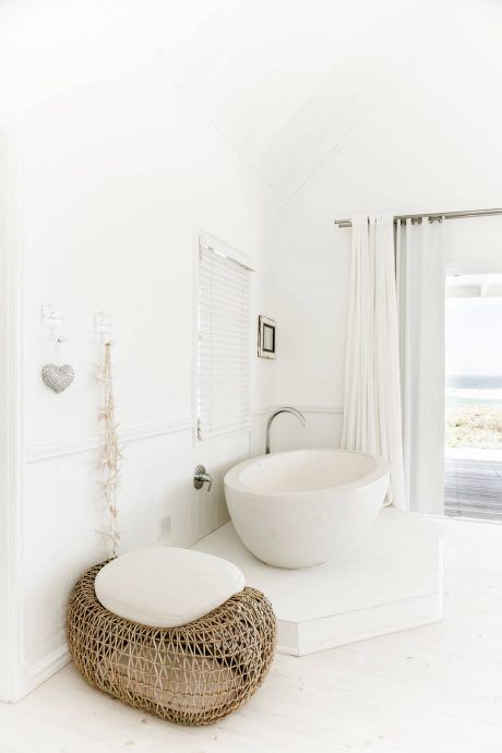 bathroom, white floor, white wall, white tub, whte curtain, rattan ottoman with white cushion