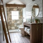 Bathroom, Wooden Look Floor, White Wall, Wooden Vanity Table, Round Mirror, White Toilet, Stone Wall