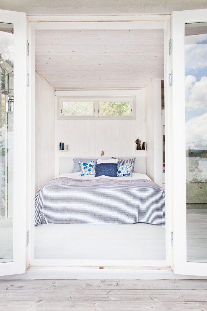 bed inside a nook, white wall, white ceiling, white floor, white floating shelves
