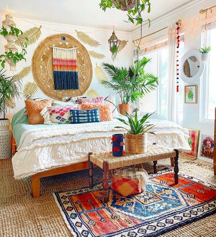 bedroom, colorful patterned rug, white wall, fringe leaves decoratioin, plants, bench, bed, round mirror