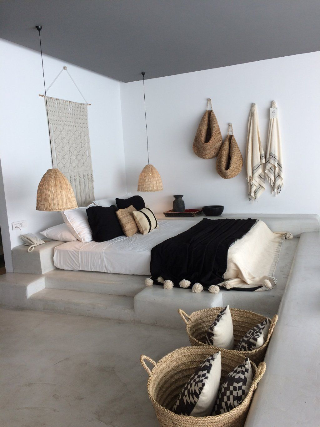 bedroom, grey seamless floor, white wall, white bedding, rattan pendants, rattan baskets