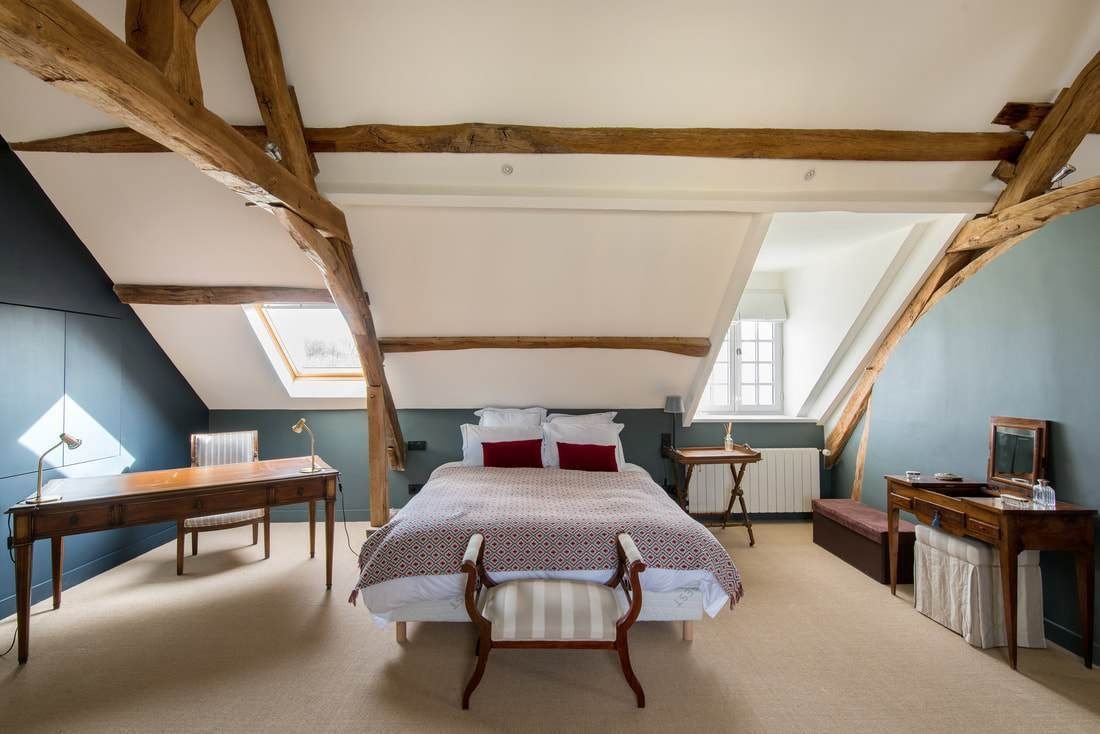 bedroom, vaulted ceiling, blue wall, white ceiling, wooden beams, bed, wooden table, white chair, wooden bench, wooden table