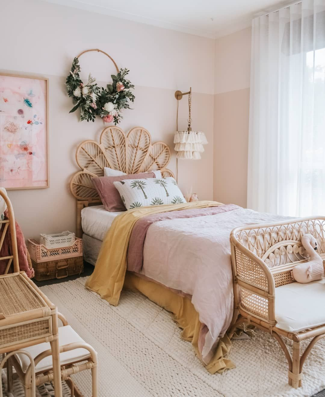 bedroom, white floor rug, pink wall, rattan bed platform, rattan sofa, suitcase side table, white fringe sconce
