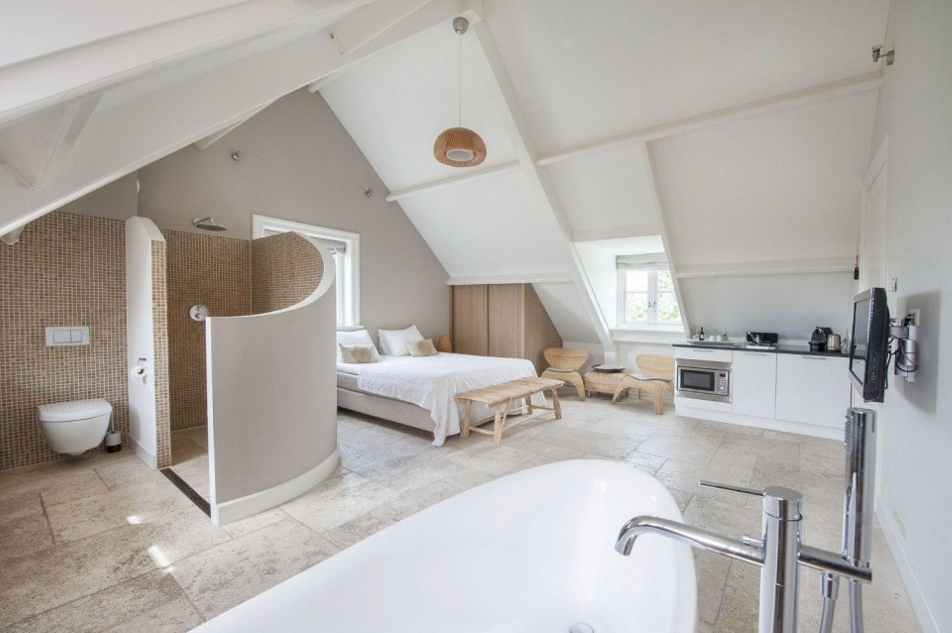 bedroom, white floor, white vaulted ceiling, bed, white kitchen pendant, open bathroom
