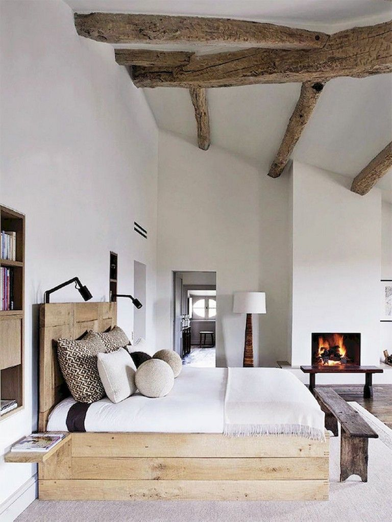 bedroom, wooden floor, white rug, wooden bed platform, wooden headboard, wooden bench, white wall, wooden beams, shelves nook with wooden boards