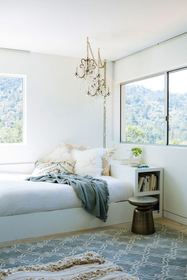 bedroom, wooden floor, white wall, chandeliers, white wooden bed platform, white shelves, glass windows, metal side table