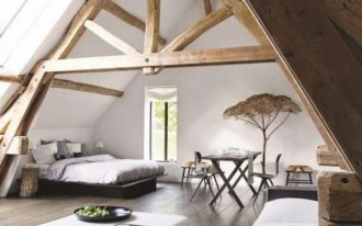 bedroom, wooden floor, white wall, wooden beams, vaulted ceiling, black bed platform, blackk sofa with white cushion