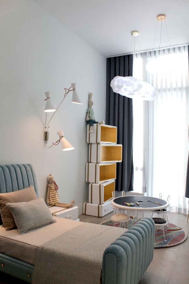 bookshelf, white stakced boxes, white sconces, blue bed frame, black rounch table