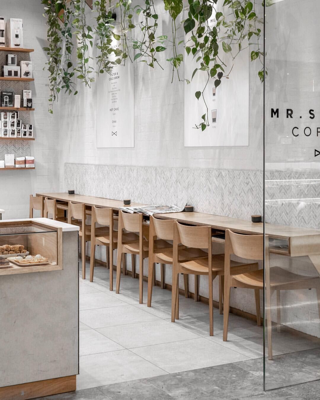 cafe, grey floor tiles, grey wall, wooden long table, wooden chairs, wooden floating shelves