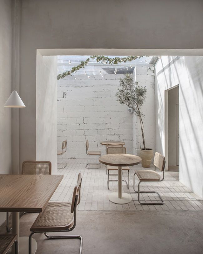 cafe, white wall, glass ceiling, wooden round table, wooden rattan chairs