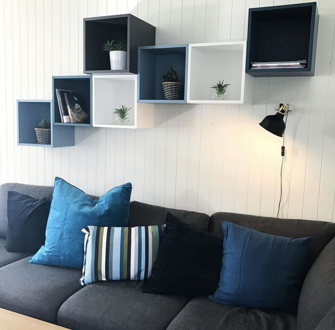 decorative shelves, blue white black square floating boxes, grey sofa, white wooden wall
