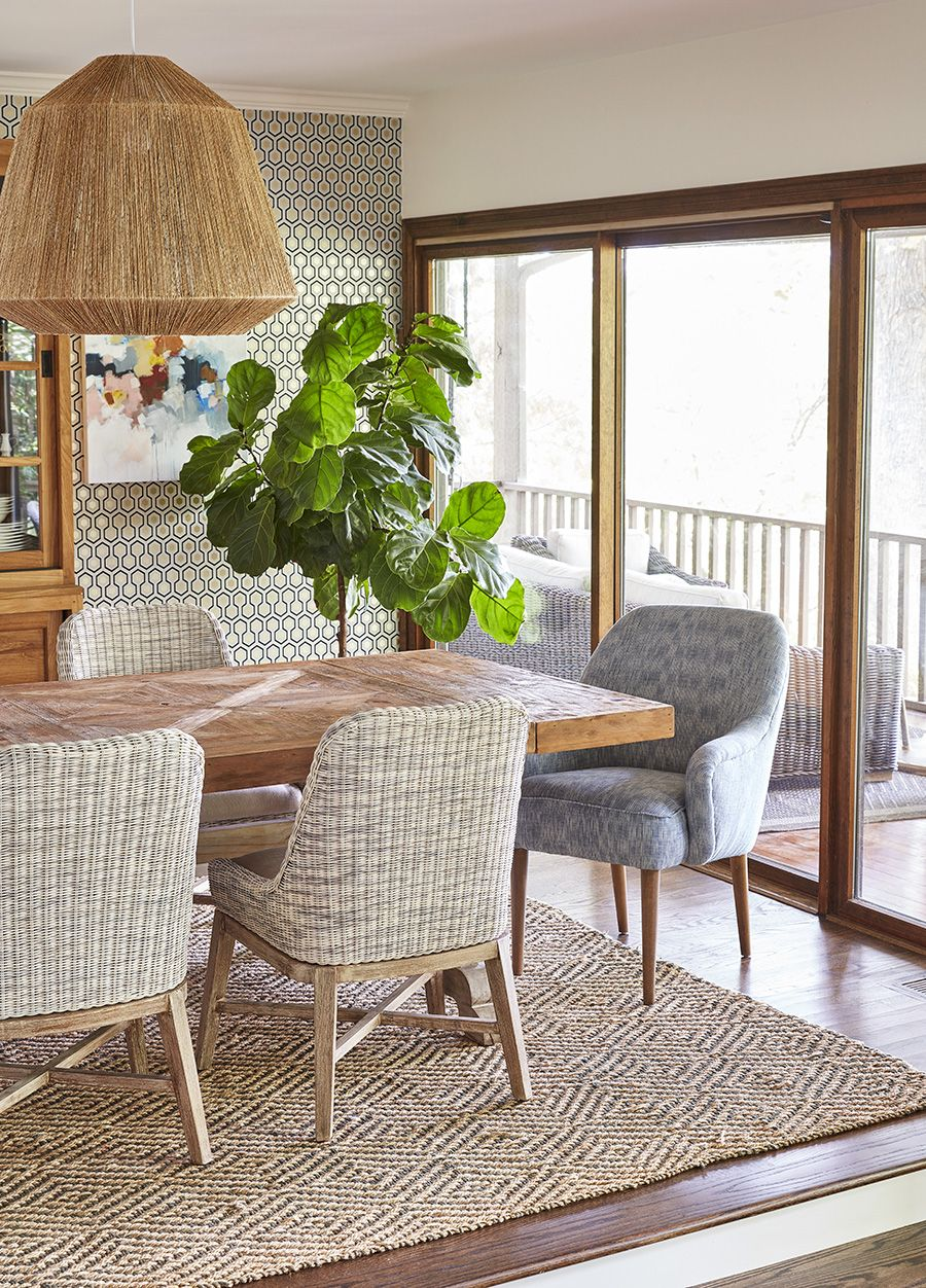 dining room, white wall, rattan pendant, wooden floor, patterned brownrug, wooden chairs with rattan seat, wooden table