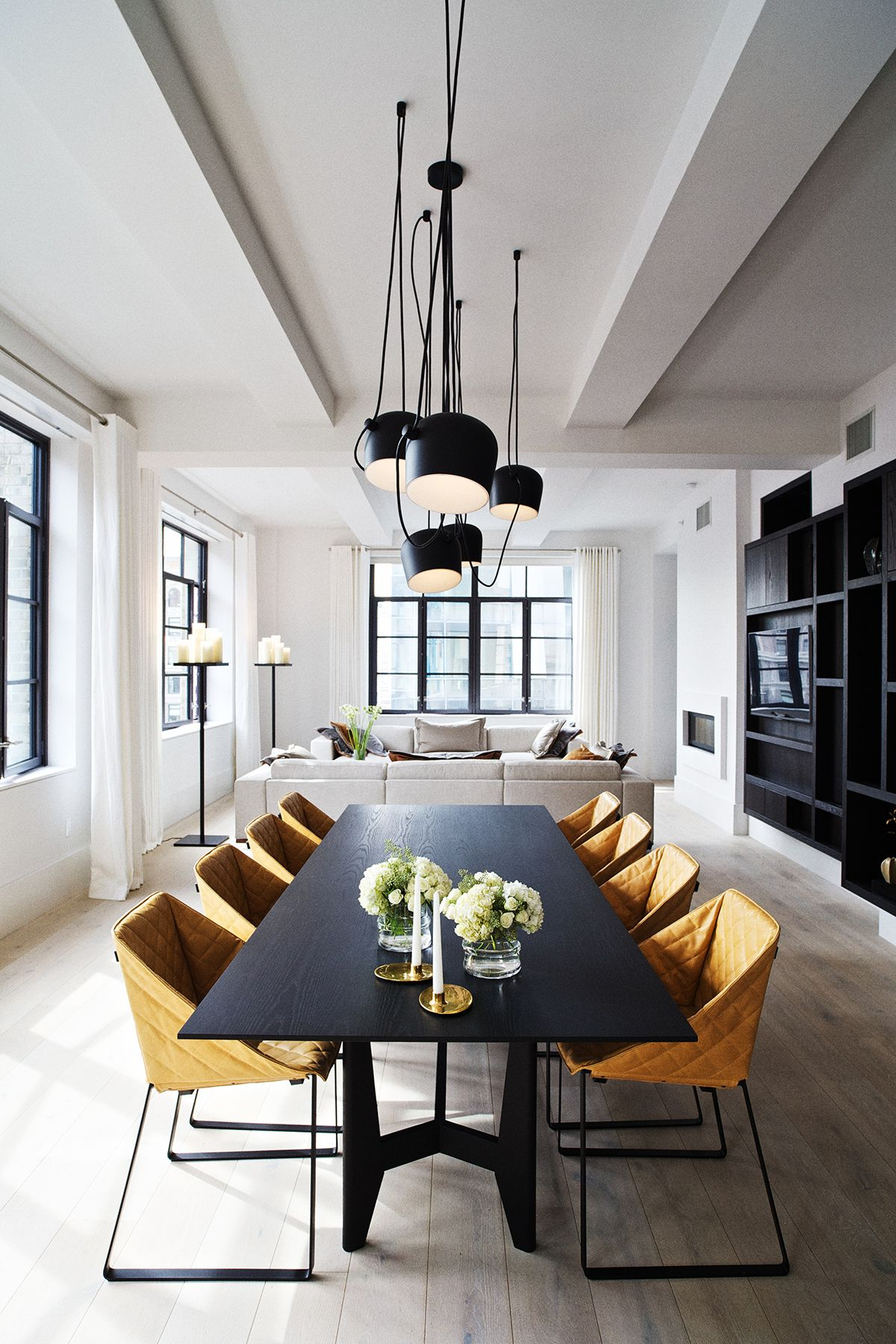 dining room, wooden floor, white wall, black dining rectangular table, brown chairs, black pendants