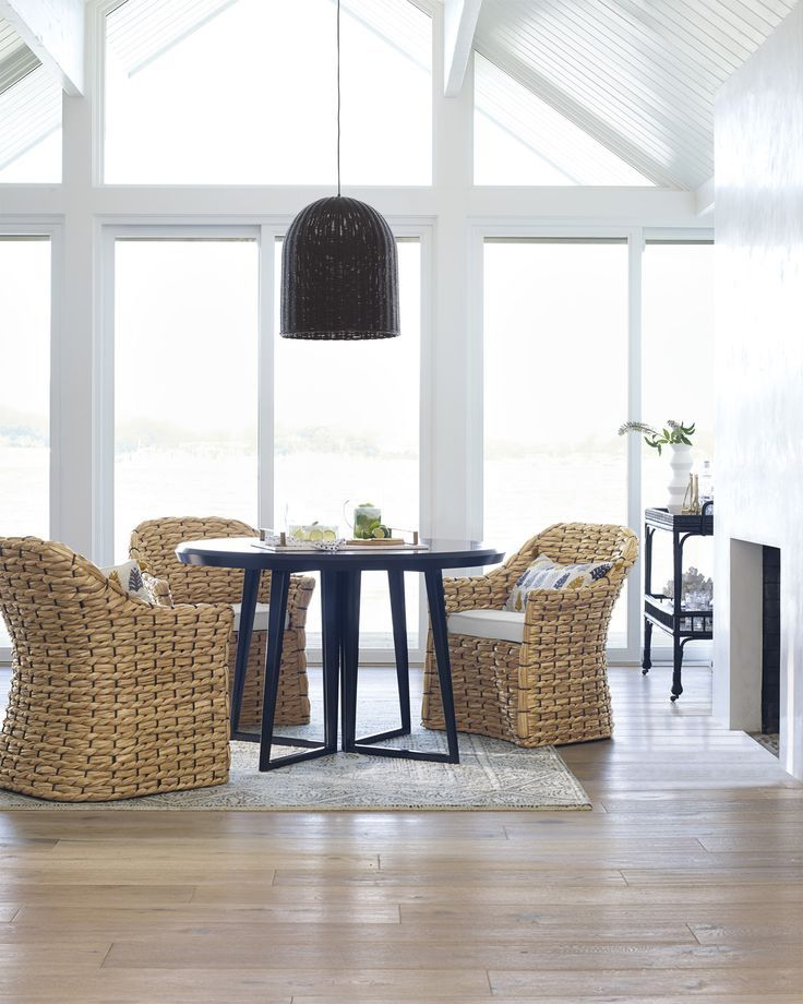 dining room, wooden floor, white wall, white ceiling, rattan chairs with white cushion, black round table, black pendant