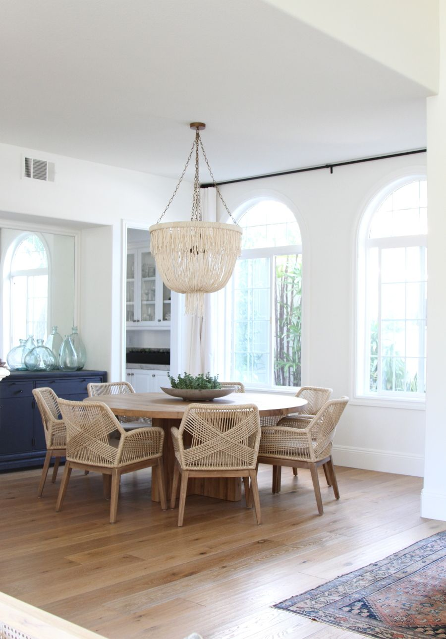 dining room, wooden floor, white wall, white chandelier, wooden round dining table, wooden chairs with rattan seating