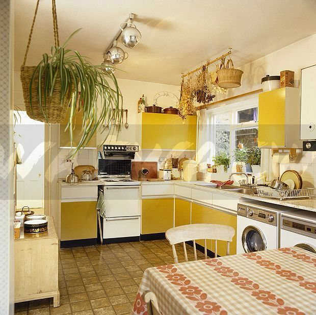 kitchen, brown floor tiles, white wall, yellow cabinet, white drawers, white top, white stove, silver ceiling lamp, rattan baskets,