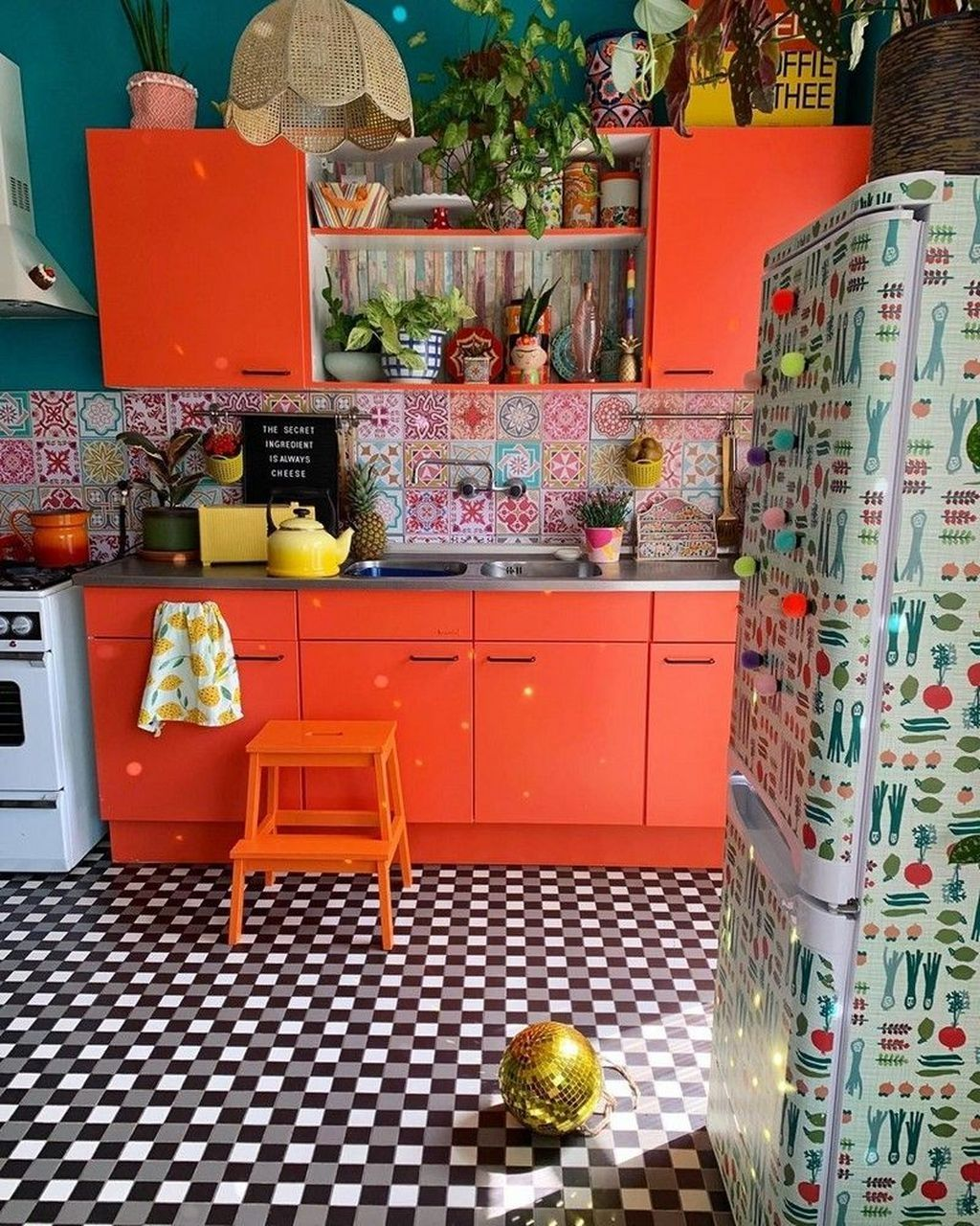 kitchen, patterned floor tiles, patterned wall tiles, orange cabinet and shelves, green wall, rattan pendant, white hood, white stove