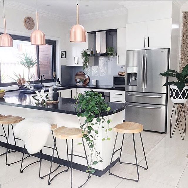 kitchen, white floor, white wall, white cabinet with black top, chopper pendants, wooden stools,