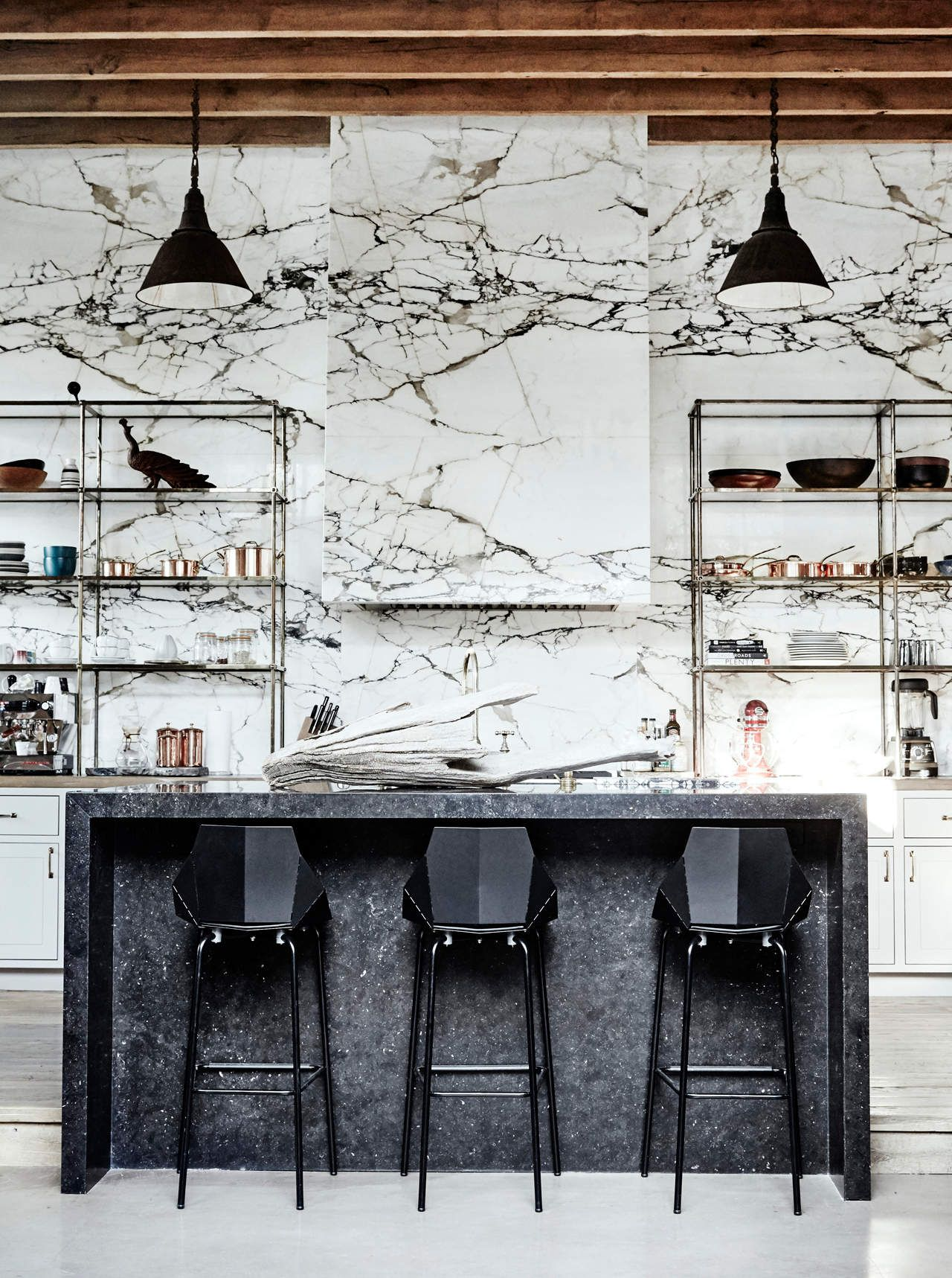 kitchen, white wooden floor, white marble wall, black pendants, black marble island, black stools, shelves