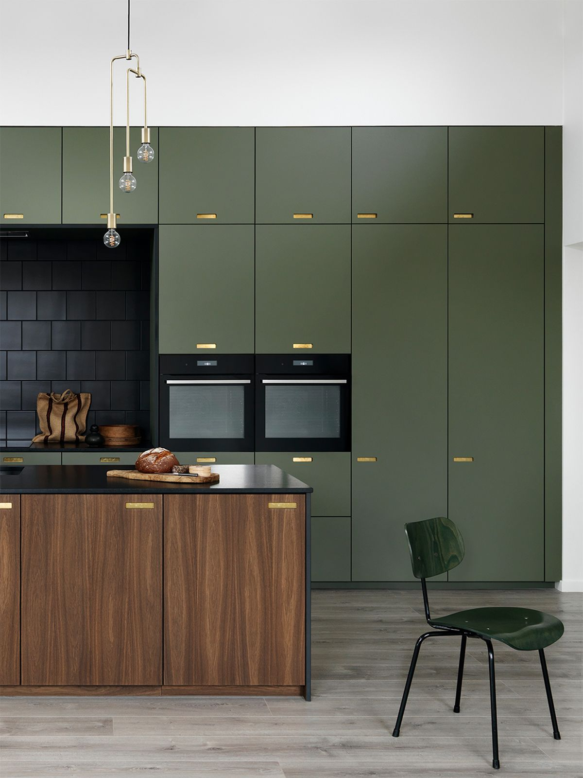 kitchen, wooden floor, white wall, green cabinet, wooden island with black top, pendants