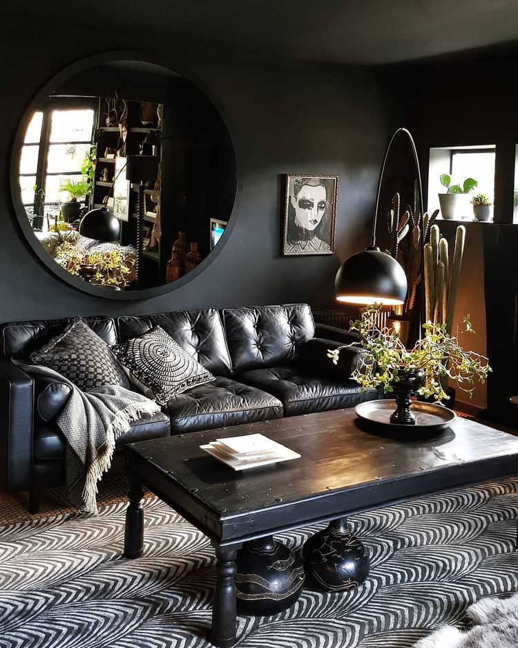 living room, black wall, blakc patterned rug, black coffee table, black leather sofa, black framed round mirror, black floor lamp