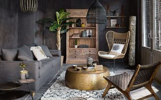 living room, grey floor, grey wall, grey sofa, rattan chairs, golden round coffee table, white patterned rug, black rattan pendant, black round side table, wooden cabinet