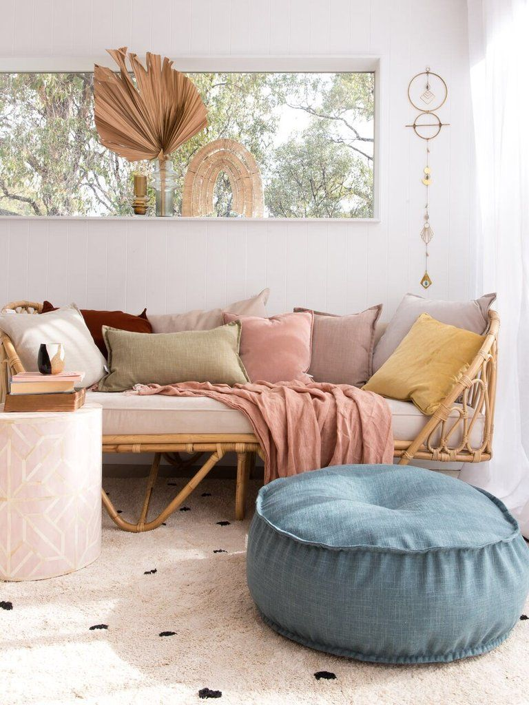 living room, light pink rug, blue round ottoman, rattan bench with white cushion, colorful pillows