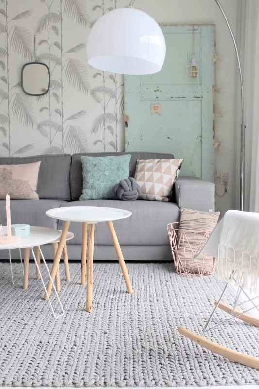 living room, patterned wallpaper, white floor lamp, grey sofa, white round tables, rocking chair