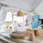 Living Room, Seamless Floor, White Wall, Vaulted Ceiling, White Soffa, Rattan And Wooden Stools, Rattan Pendant, Blue Cabinet