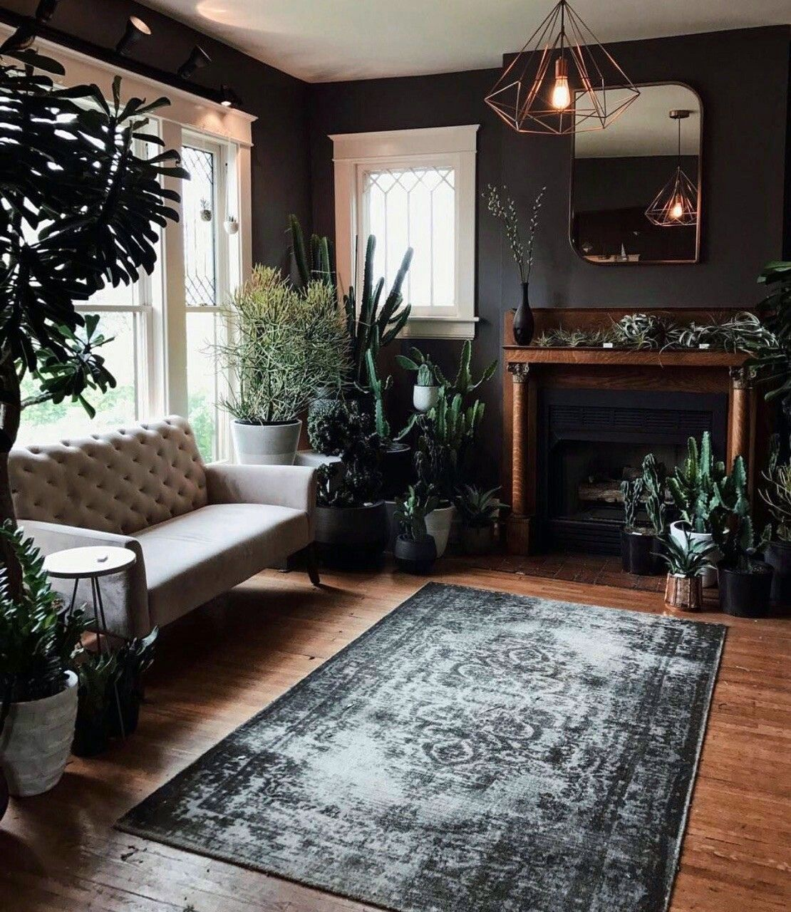 living room, wooden floor, black wall, wooden framed fireplace, white sofa, plants, golden framed pendants
