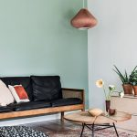 Living Room, Wooden Floor, White Wall, Green Wall, Wooden Sofa With Black Cushion, Round Wooden Coffee Table, Wooden Cabinet, Copper Pendant