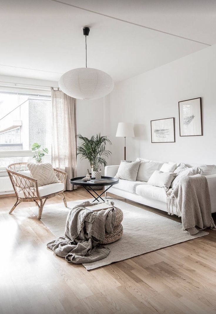 living room, wooden floor, white wall, white sofa, grey rug, rattan chair with white cushion, white pendant, rattan ottoman, black tray coffee table