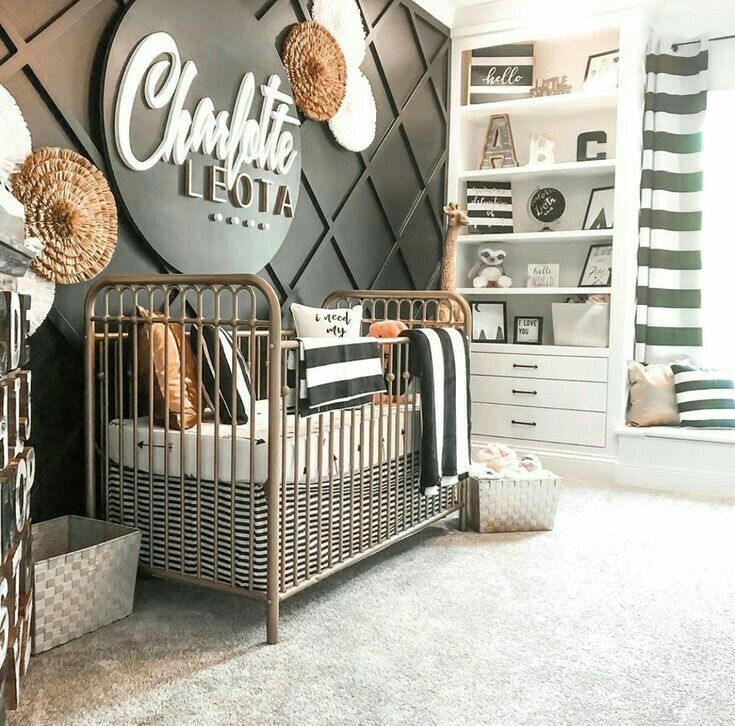 nursery, gey rug, black accent wall, iron crib, round name plat, white shelves, white window nook
