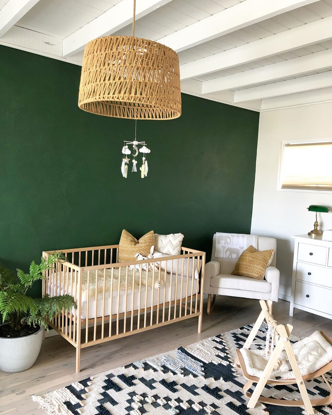 nursery, green accent wall, white wall, wooden crib, white crib, white cabinet, patterned rug