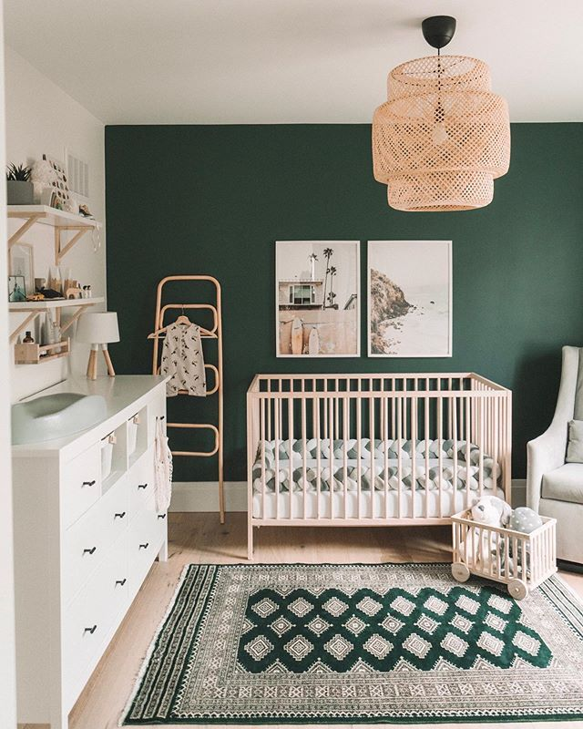 nursery, green accent wall, wooden floor, rattan pendant, white cabinet, white chair, wooden floating shelves