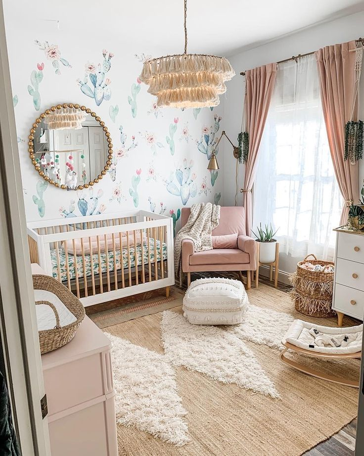 nursery, rattan rug, white patterned wall, fringe pendant, white wooden crib, pink chair, white ottoman, white cabinet, white rocking chair, pink cabinet