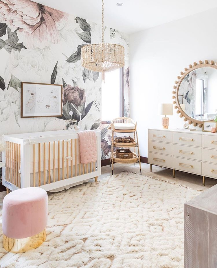nursery, white rug, wooden floor, white wall, patterned wall, white wooden crib, white cabinet, round mirror, fringe pendant