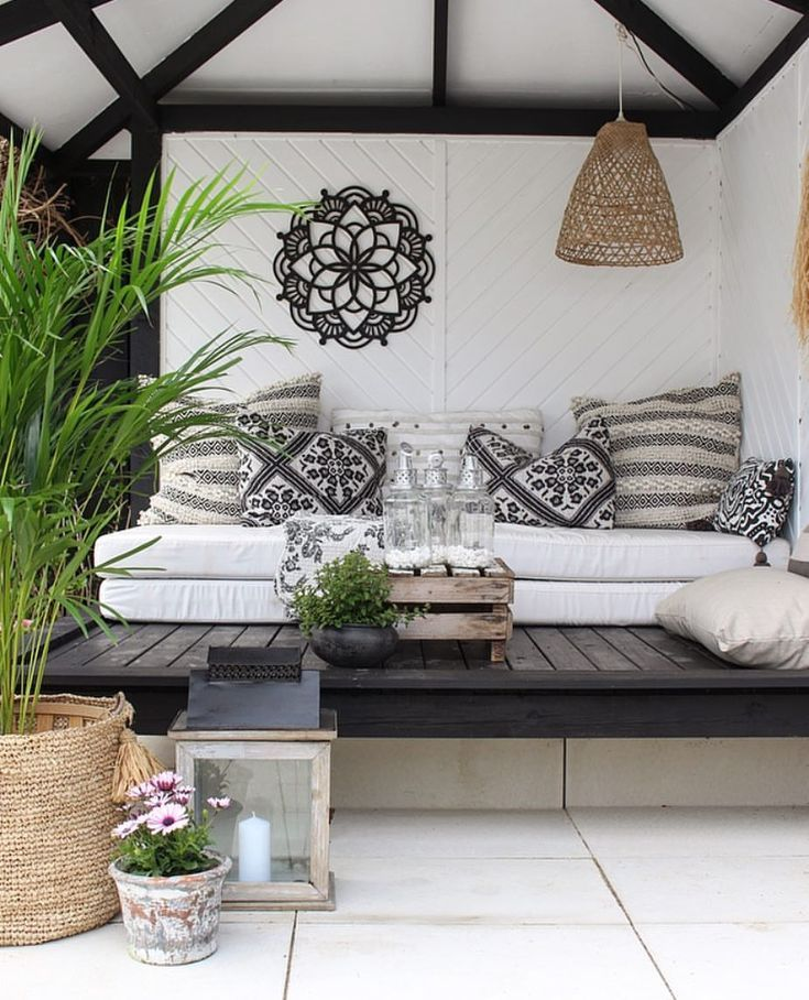 patio, black wooden stage, white cushion, white wooden wall, rattan pendant, wooden table, rattan plants pot