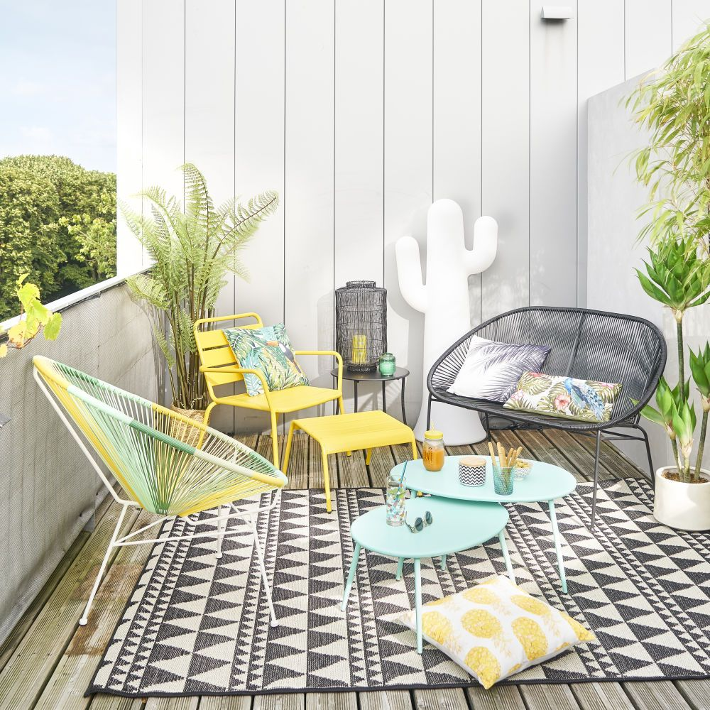 patio, wooden floor, white wooden wall, yellow chair, yellow ottoman, rattan bench and chair, blue nesting table, black white rug