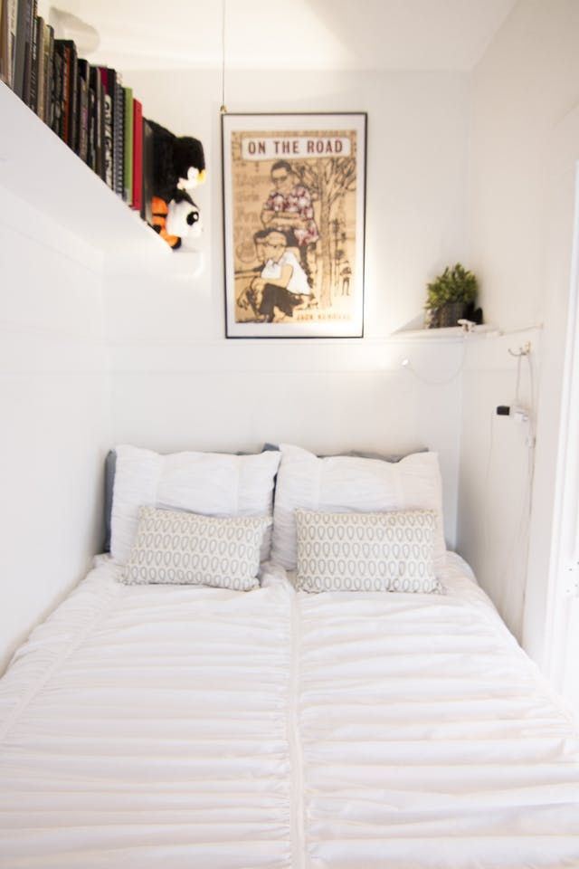small bedroom, white wall, floating shelves, white corner shelves, white sconce