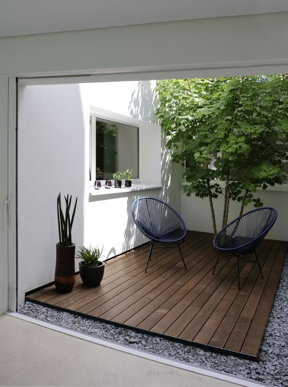 small garden, stones, wooden stage, whtie wall, floating shelves, rattan chairs, trees