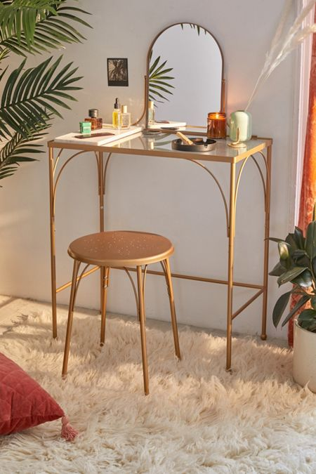 thin golden table with glass top, copper stool, small mirror