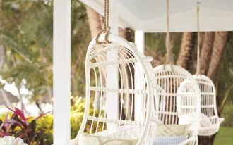 white hanging rattan chairs, pillows and cushion, white wooden floor