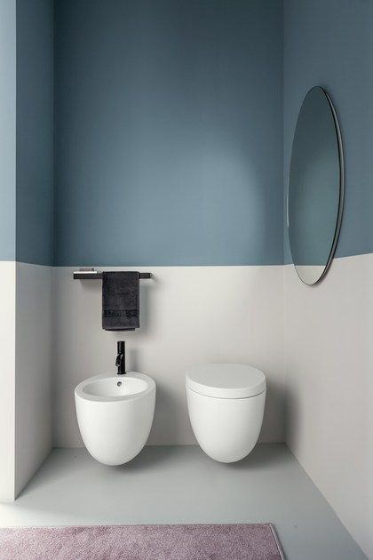 white toilet, white low sink with the same shape, blue white wall, round mirror