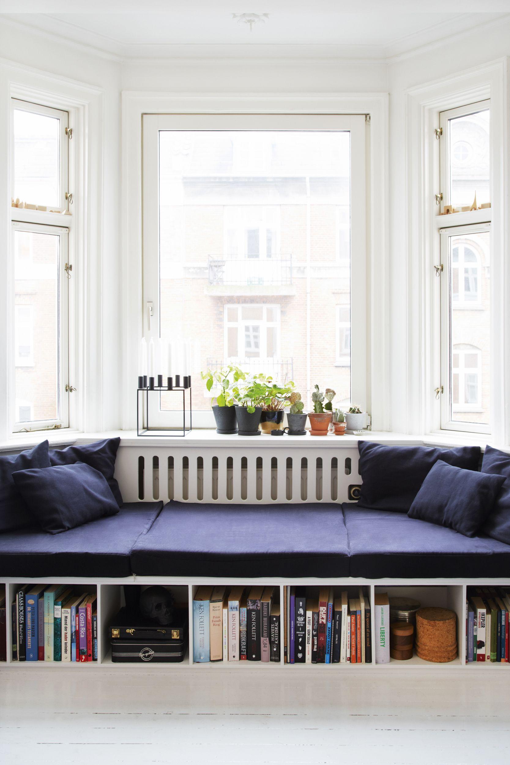 white wooden built in bench, dark blue cushion and pillows, white floor, white framed window