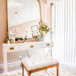White Wooden Desk, White Floor, White Pink Rug, Golden Stool With White Cushion, Golden Framed Mirror