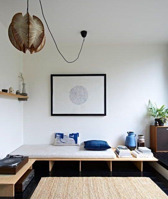 wooden board bench, white cushion, black floor, rattan rug, floating shelves
