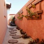 Yard, Brown Stones, Orange Wall, Wooden Plants Board, White Floor, Lounge Chair